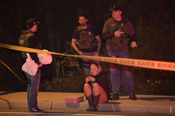 Sheriff's deputies speak to a potential witness as they stand near the scene Thursday, Nov. 8, 2018, in Thousand Oaks, Calif. where a gunman opened fire Wednesday inside a country dance bar crowded with hundreds of people on