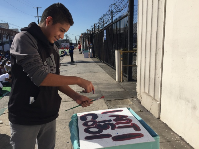 George Washington Carver Middle School 7th-grader Diego Castañeda splatters paint on his canvas, which reads