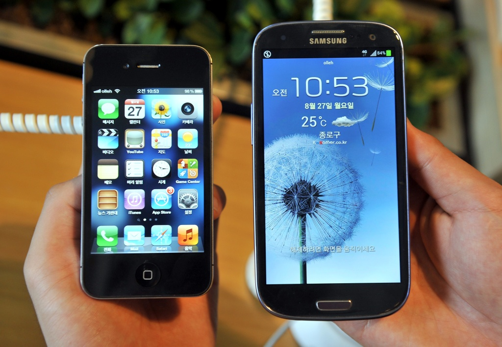 File: An employee shows an Apple's iPhone 4s (L) and a Samsung's Galaxy S3 (R) at a mobile phone shop in Seoul on August 27, 2012.