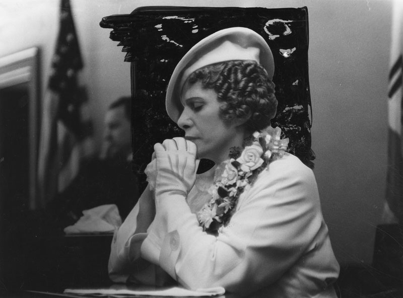 Aimee Semple McPherson, her eyes closed and hands folded, seated in what appears to be a courtroom. Circa 1937.