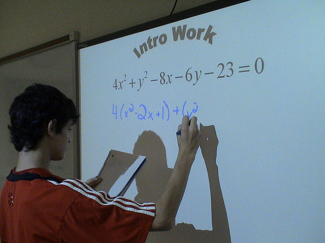 File: A student writes on a Smart Board.