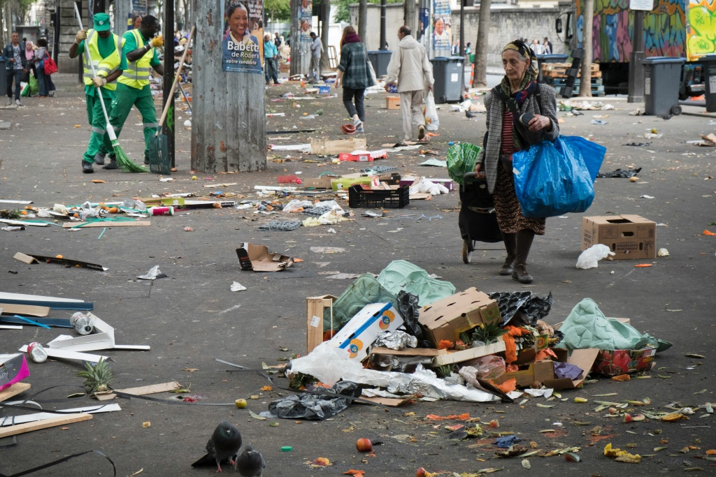 A woman walks past waste left behind after a food market in Paris on May 13, 2017.