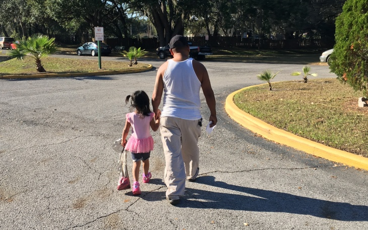 Anastausio Bautista walks with his 4-year-old to the car from her Head Start center. Driving her to and from preschool causes anxiety for the family as Bautista cannot get a driver's license because he's in the U.S. illegally. If he's pulled over, he could be arrested and deported.