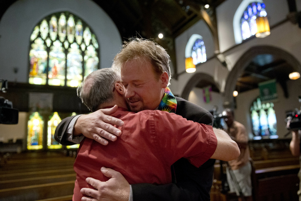 United Methodist pastor Frank Schaefer, right, hugs the Rev. David Wesley Brown after a news conference Tuesday, June 24, 2014, at First United Methodist Church of Germantown in Philadelphia. Schaefer, who presided over his son's same-sex wedding ceremony and vowed to perform other gay marriages if asked, can return to the pulpit after a United Methodist Church appeals panel on Tuesday overturned a decision to defrock him.