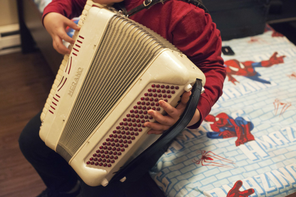 Alex, 14, plays the accordion in his bedroom. He has been learning how to play one of his dad's favorite songs, La Puerta Negra, or