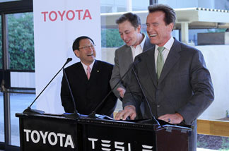 Toyota CEO Akio Toyoda, Tesla Motors CEO Elon Musk and California governor Arnold Schwarzenegger laugh during a news conference at Tesla Motors headquarters May 20, 2010 in Palo Alto, California.