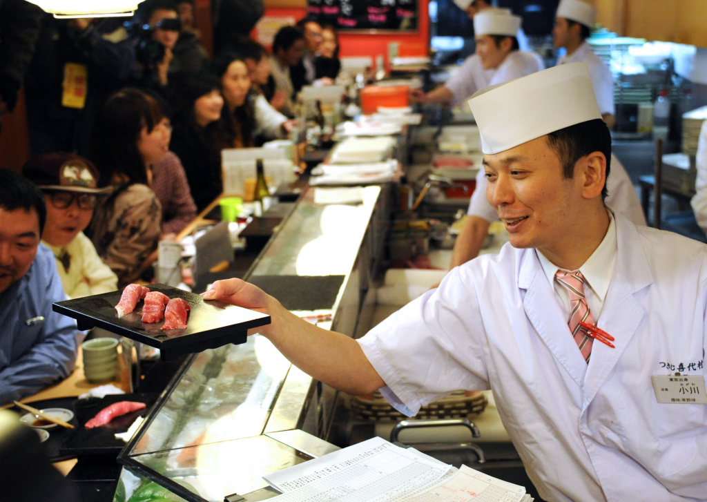 A sushi chef (R) serves up tuna sushi made from a 222-kg (488-pound) bluefin tuna, purchased earlier in the day for a record price and sliced up for customers at the main restaurant of the popular Japanese chain Sushi-Zanmai near Tokyo's Tsukiji fish market on January 5, 2013.