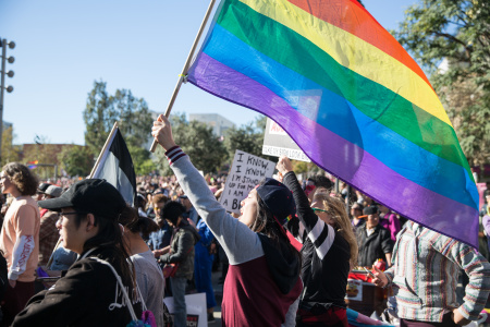 An attendee of the 2018 Los Angeles Women's March waving a rainbow flag.