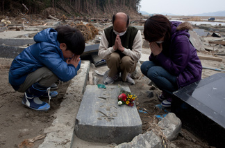 A month after the tsunami divastation, a family prays by a grave in Ishinomaki, Miyagi prefecture on April 11, 2011.