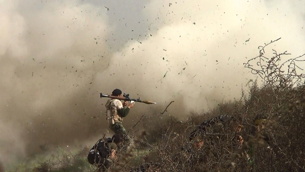 An image grab taken from a video shows opposition fighter holding a rocket propelled grenade (RPG) as his fellow comrades take cover from an attack by regime forces on August 26, 2013.