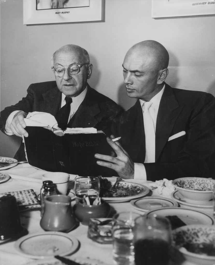 Director Cecil B DeMille and actor Yul Brynner discussing a passage from the Holy Bible, prior to the filming of their movie 'The Ten Commandments', circa 1955.