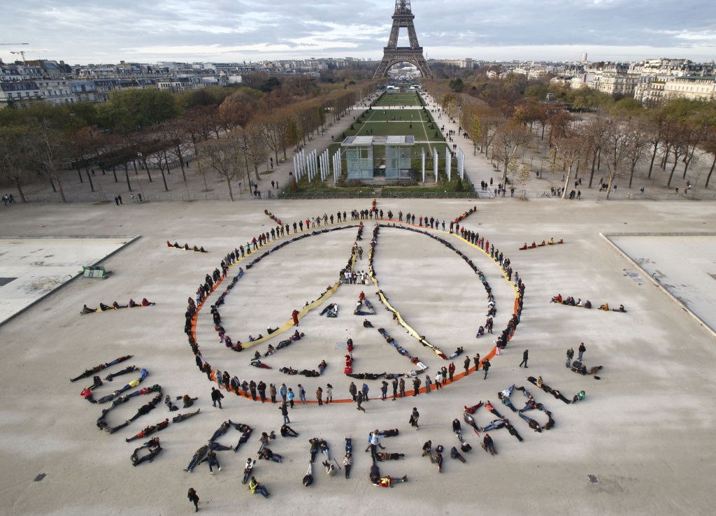 Environmental activists form a human chain near the Eiffel Tower in Paris on the sideline of the COP21 United Nations Climate Change Conference. With a historic agreement on the line, hundreds of diplomats in Paris are preparing to extend the U.N. climate change conference into Saturday. It was supposed to end Friday.