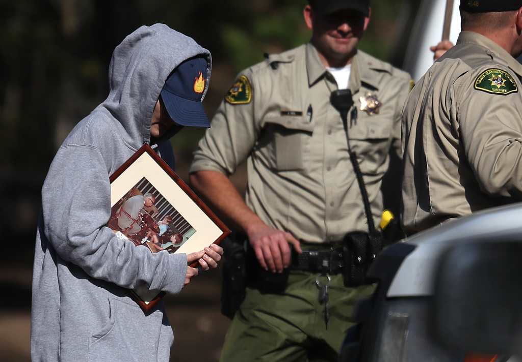 MONTECITO, CA - JANUARY 11:  A resident holds a family photo that was retreived from a home that was destroyed by a mudslide on January 11, 2018 in Montecito, California. 17 people have died and hundreds hundreds of homes have been destroyed or damaged after massive mudslides crashed through Montecito, California early Tuesday morning.  (Photo by Justin Sullivan/Getty Images)