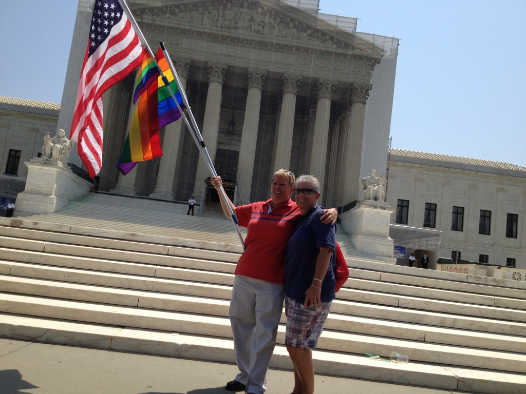 Gay rights supporters pose in front of the Supreme Court after Wednesday's decision on DOMA and Proposition 8.