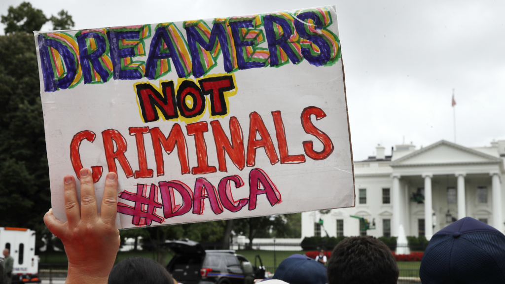 FILE: A woman holds up a signs in support of the Obama administration program known as Deferred Action for Childhood Arrivals, or DACA, during a rally on Aug. 15 at the White House.