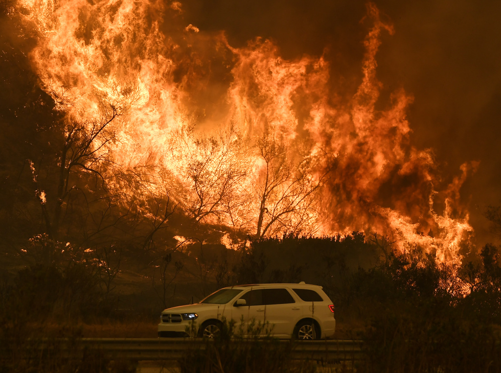 Vehicles pass beside a wall of flames on the 101 highway as it reaches the coast during the Thomas wildfire near Ventura, California on December 6, 2017.
