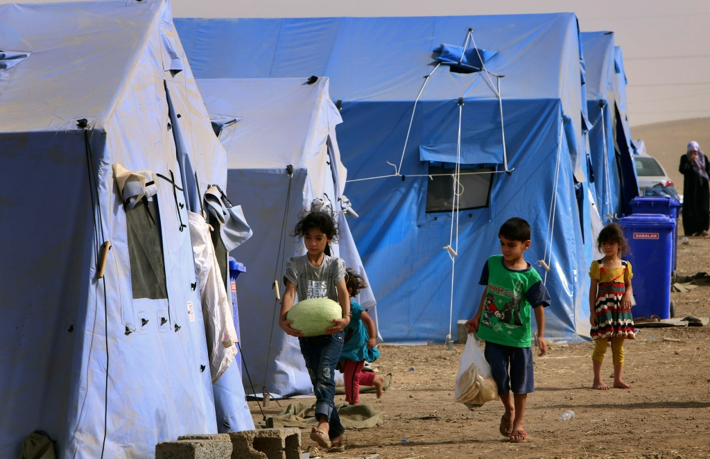 Children walk outside temporary tents set up to shelter Iraqis fleeing violence in Iraq's northern Nineveh province. As many as half a million people are thought to have fled Mosul, which was captured in June by the Islamic State of Iraq and the Levant (ISIL).