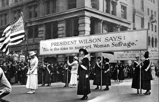 Women suffragists marching during the presidency of Woodrow Wilson.