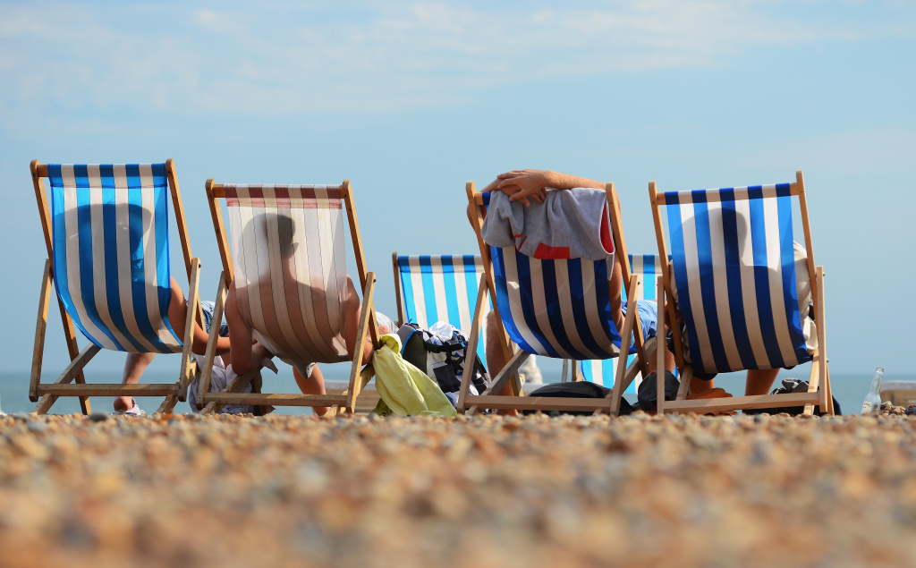 File: People relax in deck chairs during the hot weather on Brighton beach on August 1, 2013 in Brighton, England.