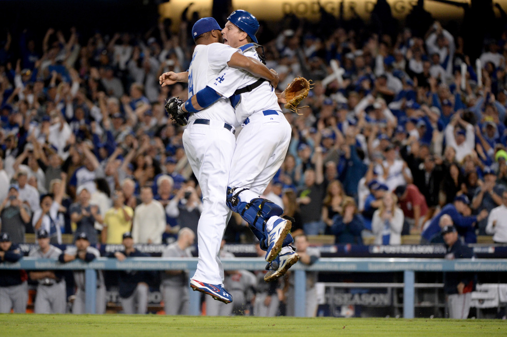 Catcher A.J. Ellis #17 and Kenley Jansen #74 of the Los Angeles Dodgers celebrate after the Dodgers defeat the Atlanta Braves 4-3 in Game Four of the National League Division Series at Dodger Stadium on October 7, 2013 in Los Angeles, California.