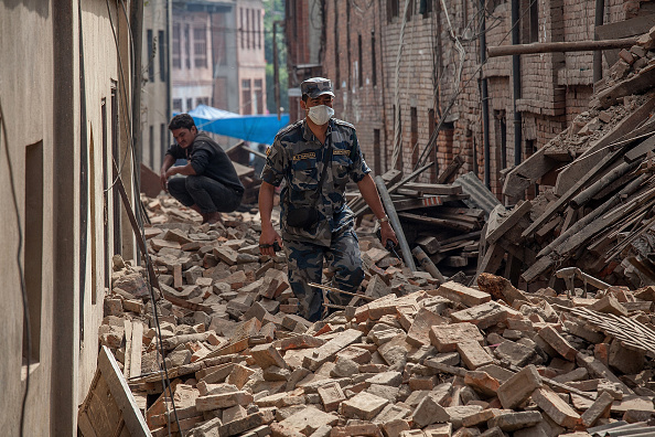 A member of police forces walks down a street covered in debris after buildings collapsed on April 26, 2015 in Bhaktapur, Nepal.