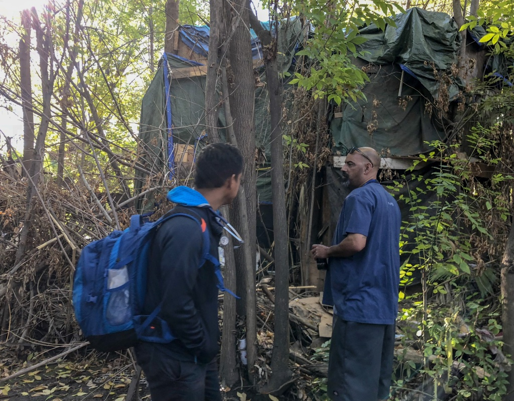 Outreach worker Eric Montoya (right) and Dr. Absalon Galat (left) approach a makeshift shelter in the Sepulveda Dam basin, in Los Angeles' San Fernando Valley