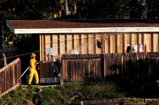 Fire department officials spray retardant on a structure next to the home of George Jura Jakubec before it was set ablaze by officials December 9, 2010 in Escondido, California.