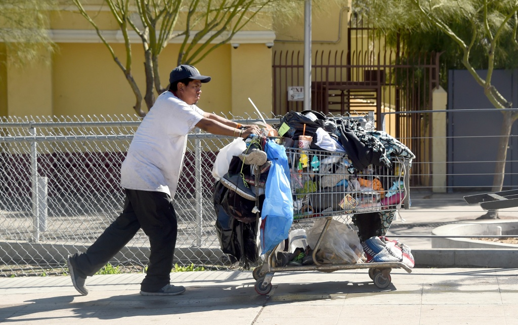 A man pushes a shopping cart full of belongings along a street in Los Angeles, California on February 9, 2016. Los Angeles City and County officials are voting February 9 on plans aimed at ending homelessness in the community, mostly by making permanent housing available to the tens of thousands of people who are homeless.  / AFP / Frederic J. BROWN        (Photo credit should read FREDERIC J. BROWN/AFP/Getty Images)