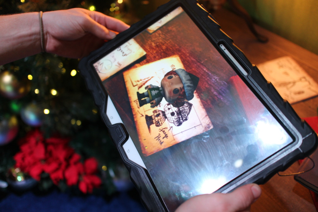 An augmented reality image of an elf is shown on a tablet screen as part of the HGTV Santa HQ attraction at Lakewood Center mall.