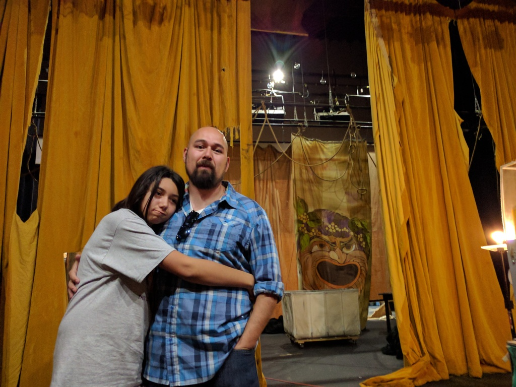 Everardo Landero (R) and his daughter Victoria standing on the theatre's stage at Santa Ana College. Everardo has his green card and plans to apply for U.S. citizenship.