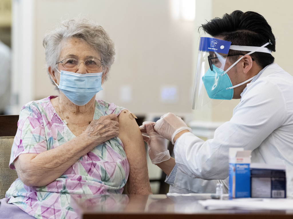 A CVS pharmacist gives the Pfizer/BioNTech COVID-19 vaccine to a resident at the Emerald Court senior living community in Anaheim, Calif., in January. Federal health officials have revised advice on nursing home visitations for the first time since September.