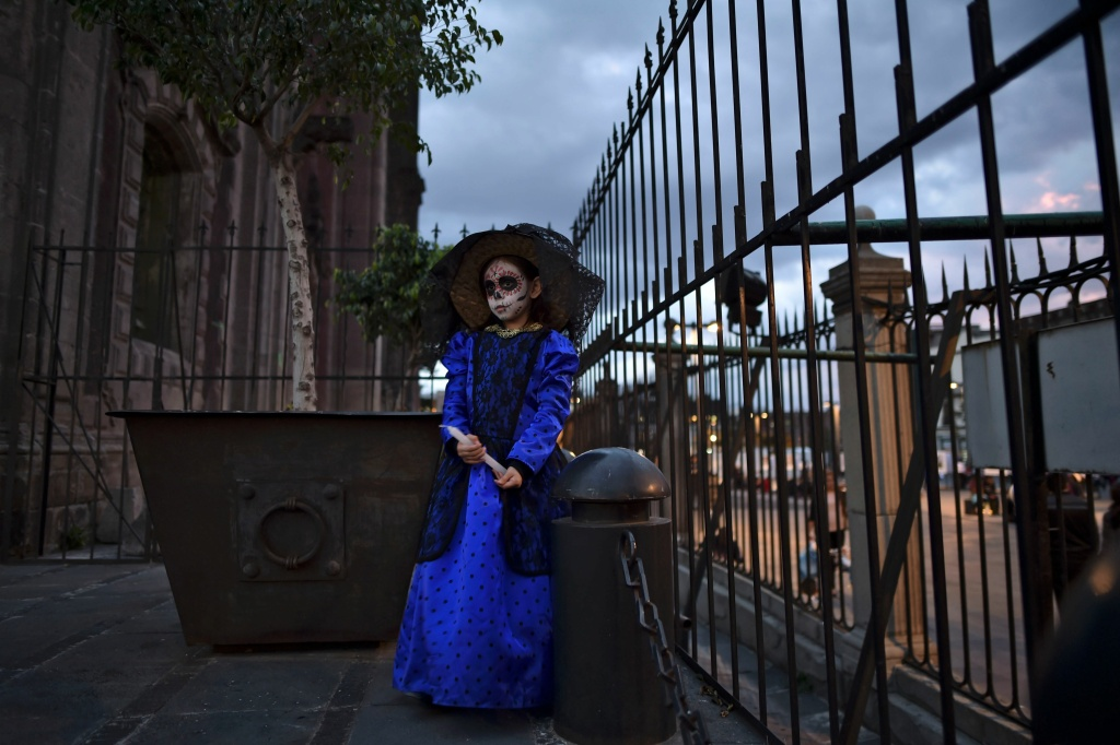 A girl dressed as Catrina is seen during a protest against femicides in Mexico City on November 1, 2016.