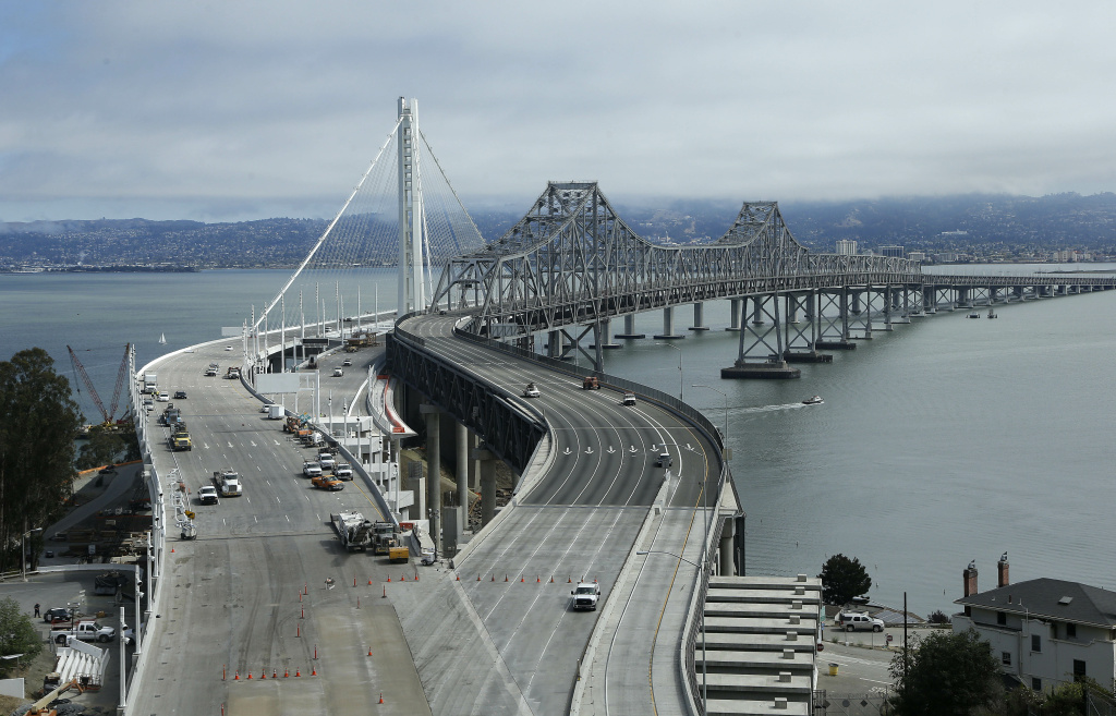 The self-anchored suspension of the new eastern section of the San Francisco-Oakland Bay Bridge, left, runs behind the current eastern section which is closed to traffic in San Francisco, Thursday, Aug. 29, 2013. Commuters faced their first morning on Thursday without the bridge, but there weren't major traffic snarls as day broke across the Bay Area. (AP Photo/Jeff Chiu)