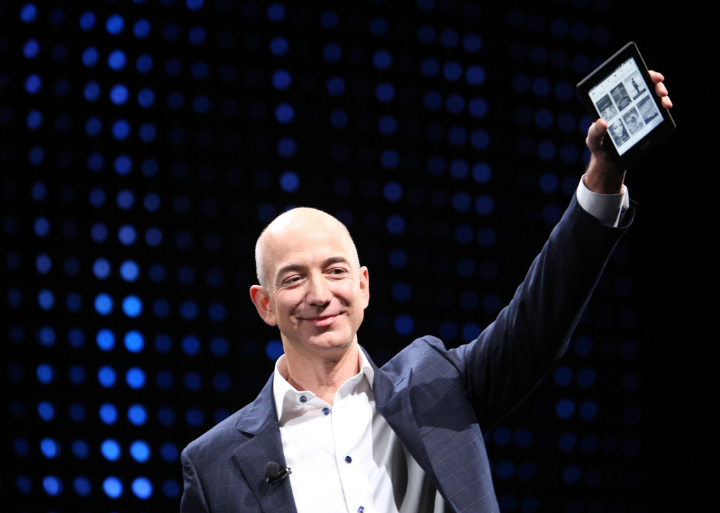Amazon CEO Jeff Bezos holds a new front-lit Kindle during a press conference on September 6, 2012 in California. Bezos bought out the Washington Post yesterday for $250 million.