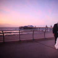 Newlyweds walk along the promenade after getting married.
