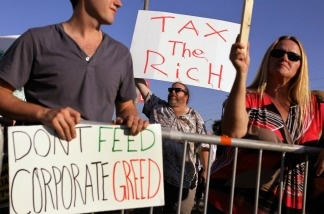 Craig Glaser holds a sign reading, 'Tax the Rich,' outside the building where the Republican presidential debate sponsored by CNN and The Tea Party Express is being held at the Florida State fairgrounds on September 12, 2011 in Tampa, Florida.