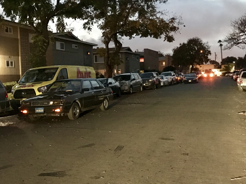 Cars double parked along an Anaheim street at dusk.