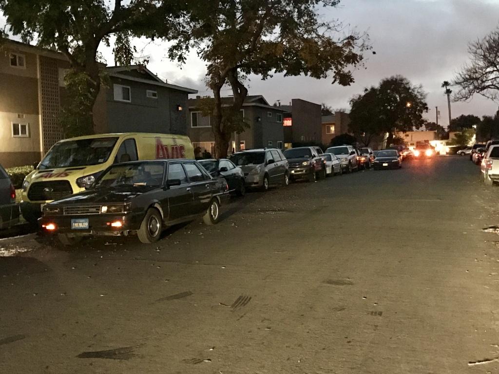 Cars double parked along an Anaheim street at dusk.