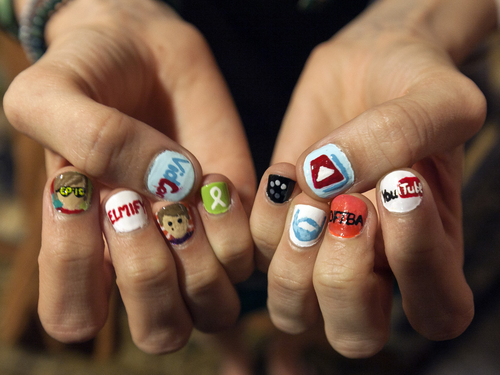File: In this Thursday, June 28, 2012 photo, Kimmy Fiorentino, from North Carolina, shows her decorated nails with YouTube video channels at VidCon at the Anaheim Convention Center in Anaheim, Calif.