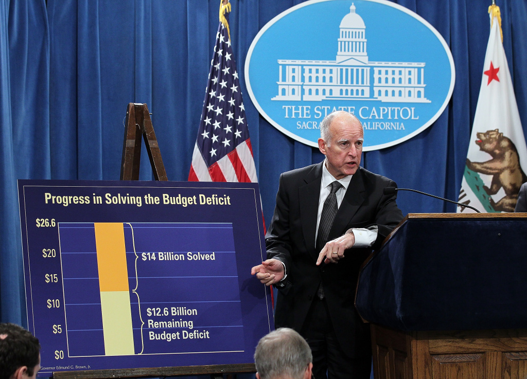 California Gov. Jerry Brown points to a chart that shows dollar amounts in the millions that were cut from the State's budget following a bill signing on March 24, 2011, in Sacramento.