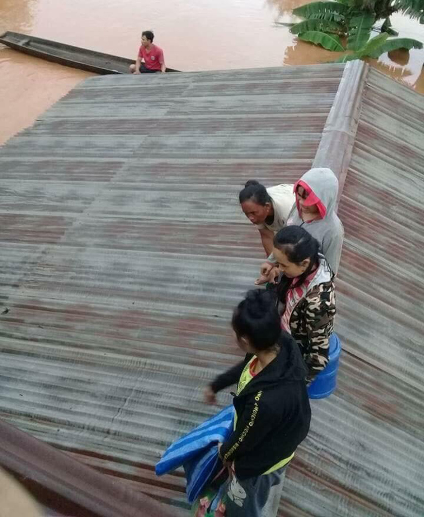 Villagers take refuge on a rooftop above floodwaters from a collapsed dam in southeastern Laos on Tuesday after a newly built hydroelectric dam was breached in southeastern Laos.