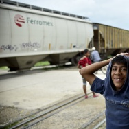 "A child remains near to the railroad as the train known as ""La Bestia,"" or The Beast, goes by in Arriaga, Chiapas state, Mexico. As more recently arrived child migrants from Central America navigate the crowded U.S. immigration court system, the federal government is kicking in money to help provide them with legal representation."