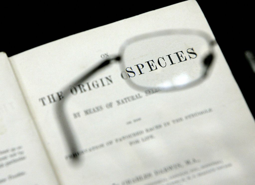 Reading glasses are held over the first printed edition of the book 'Origin of Species' (1859) by Charles Darwin at London's Natural History Musuem, 08 June 2006.