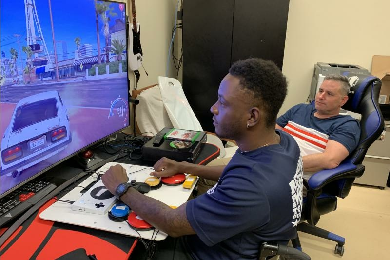 Army veteran Mike Monthervil (left) uses an adaptive controller to play video games as his VA recreational therapist Jamie Kaplan watches.