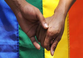 Two hands embrace in front of a rainbow flag. File photo.