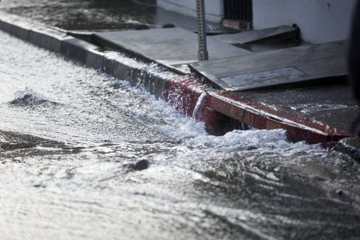 Chad Newlee, a line patrol mechanic for Los Angeles Department of Water and Power, works to pump water out of the back of an apartment building in order to check electric panels after an 18-inch main burst in Hollywood early Wednesday morning, Feb. 18, 2015 releasing a torrent of water onto residential streets and submerging cars.