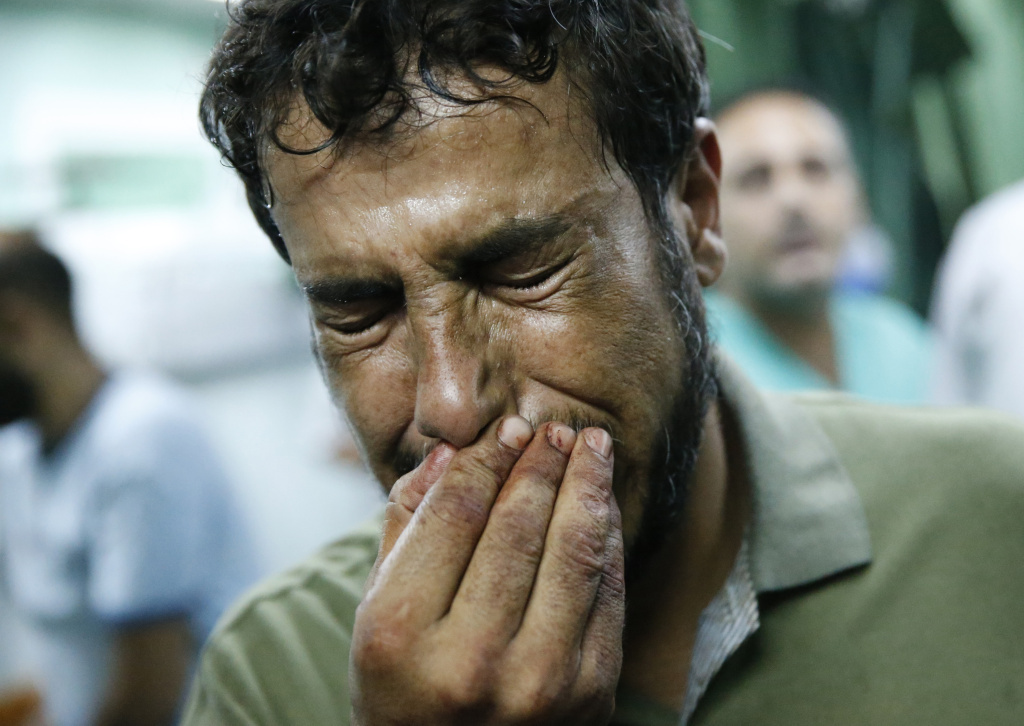 A Palestinian man cries after bringing a child, wounded in a strike on a compound housing a U.N. school in Beit Hanoun, in the northern Gaza Strip, to the emergency room of the Kamal Adwan hospital in Beit Lahiya on Thursday.