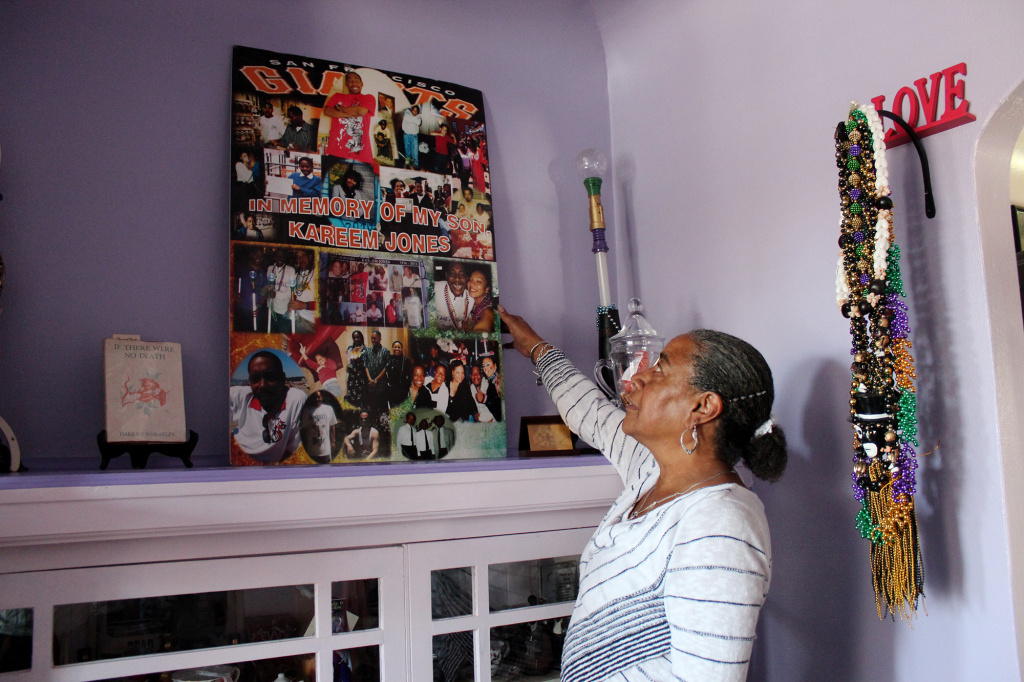 NeDina Brocks-Capla stands in her living room in San Francisco. She made a shrine filled with memories of son Kareem Jones, who died of sickle cell disease in 2013.