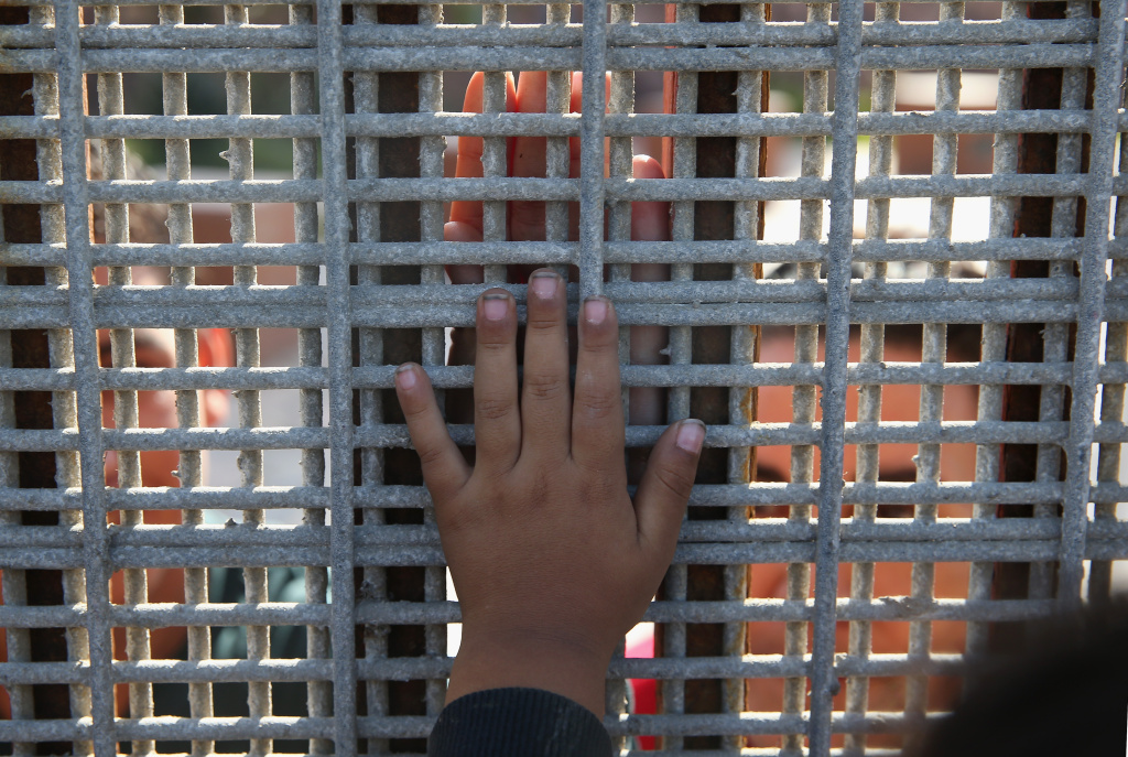 Family members reunite through bars and mesh of the U.S.-Mexico border fence at Friendship Park on November 17, 2013 in San Diego, California. According to a new report looking at two decades of deportations, immigration laws are administered more strictly on the border than they are in the U.S. interior.