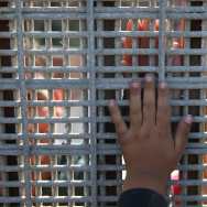 Family members reunite through bars and mesh of the U.S.-Mexico border fence at Friendship Park on November 17, 2013 in San Diego, California. A recent settlement between the American Civil Liberties Union and the Department of Homeland Security could allow some people who were voluntarily repatriated to Mexico to come back.